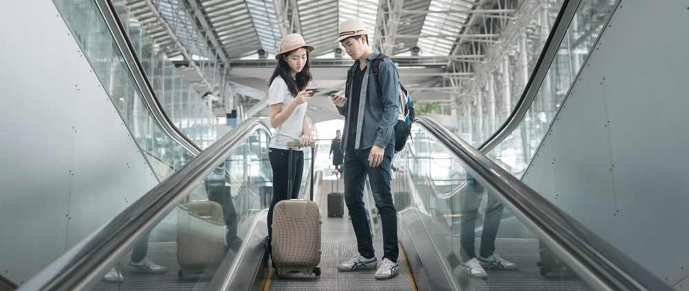 Young Asian Couple With Luggage Down The Escalator In Airport Travel