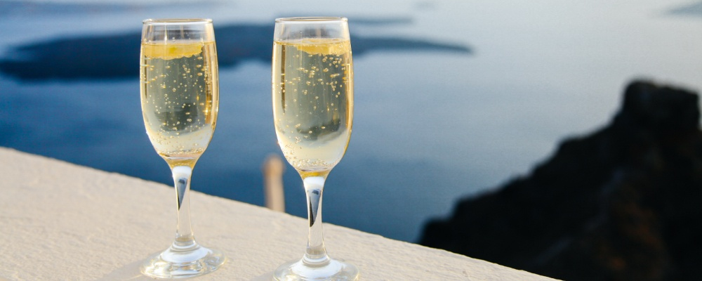 Two glasses of champagne on the edge of a balcony with an ocean backdrop