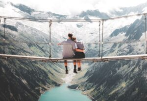 Couple on bridge suspended above a mountain valley