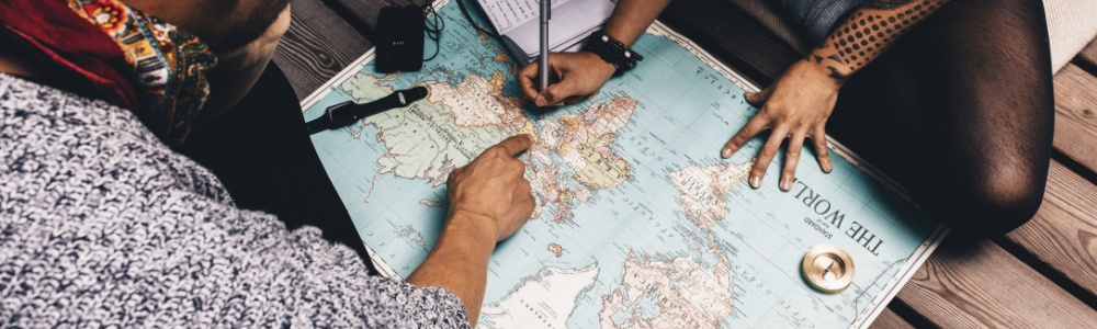 Two travelers examine a world map