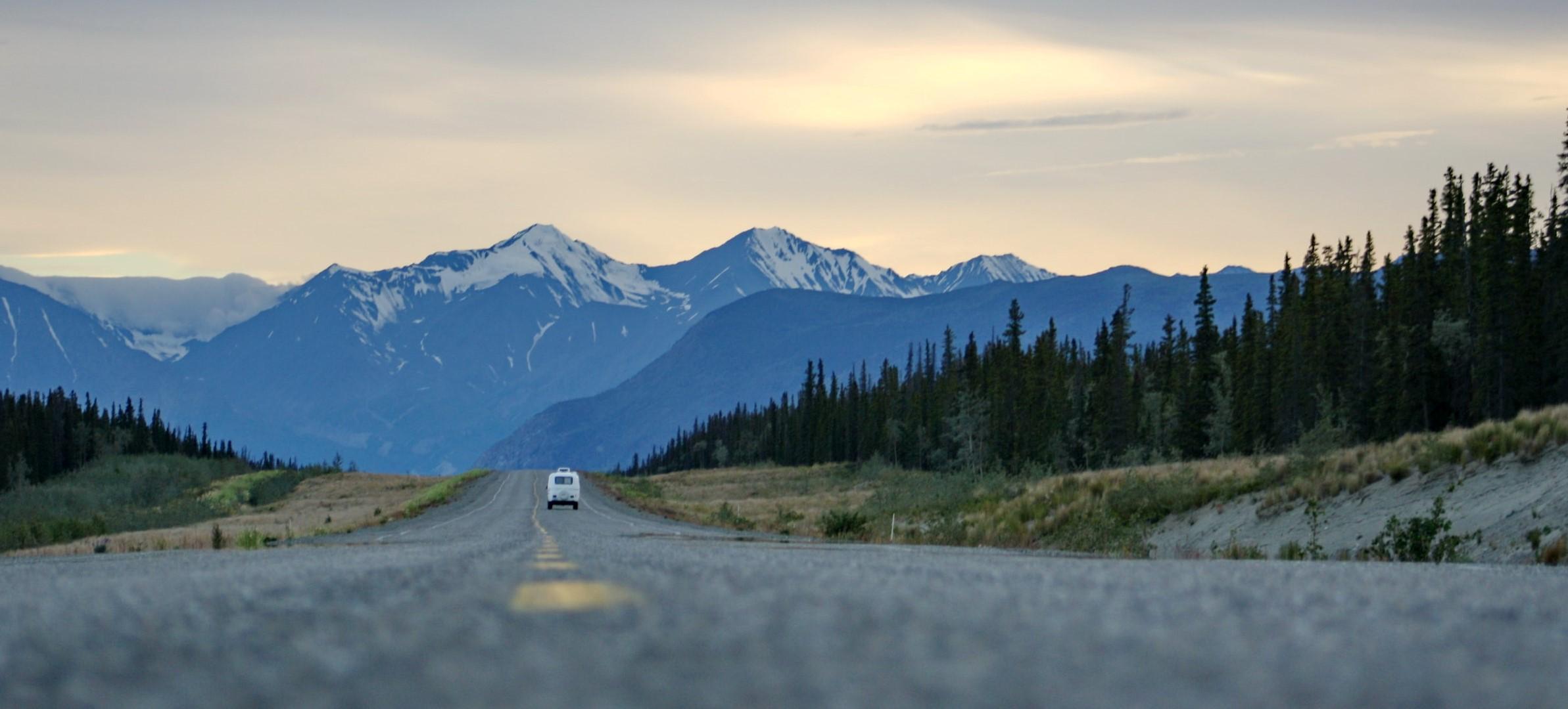 Car driving down a road toward a snowy mountain range