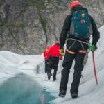 3 hikers trekking next to a frozen stream
