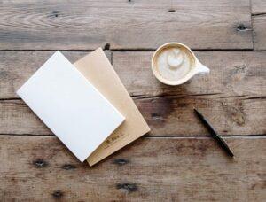 Notecard, coffee mug, pen on wooden table