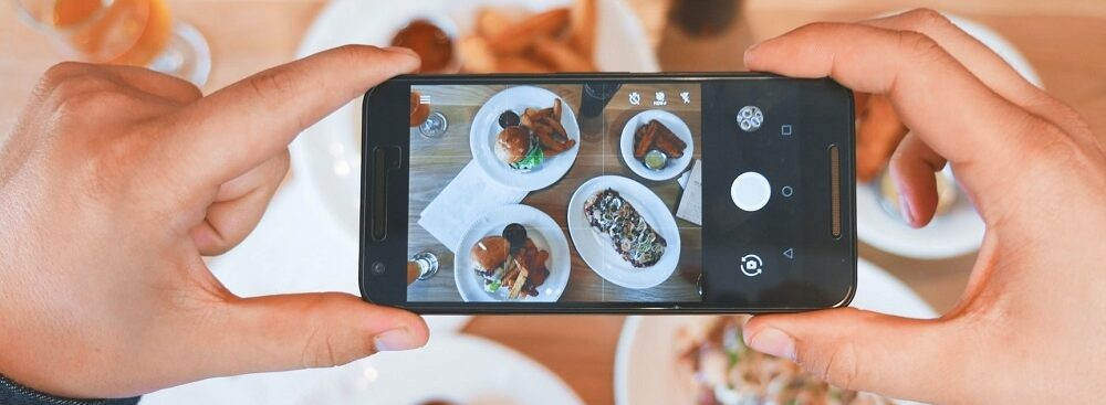 Cell phone taking a photo of restaurant dishes